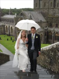 Wedding couple climbing steps of St Davids Cathedral