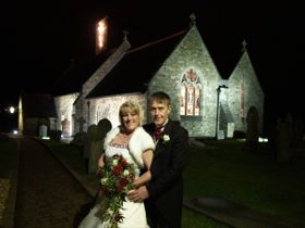Wedding couple photographed in front of church at night