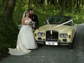 Wedding couple by Rolls Royce car